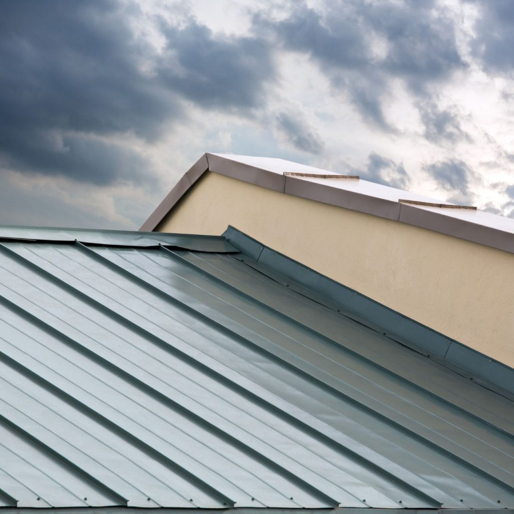 green metal roof on a stucco house