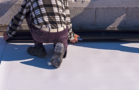 A Man Installing a Single Ply Roof.
