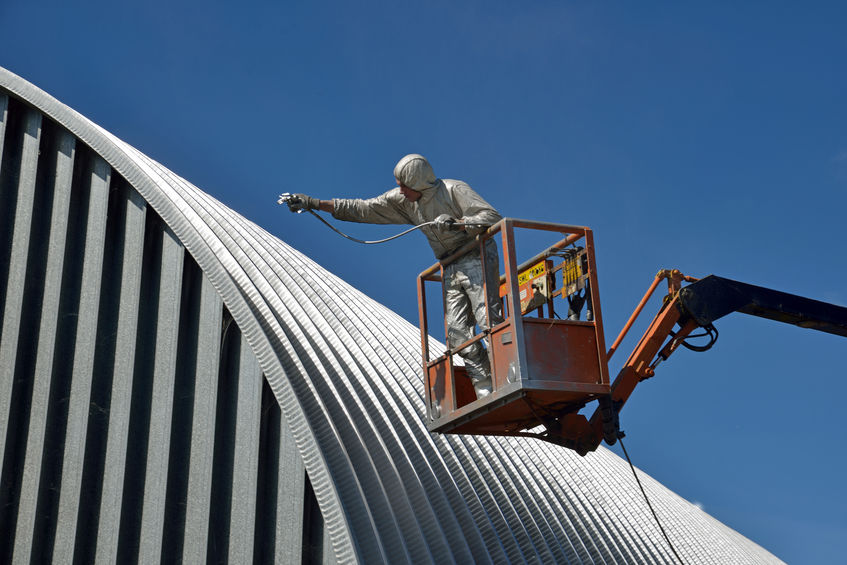Contractor Spraying Roof Coating on Building